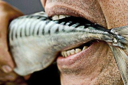 Мужчина ест сырую рыбу